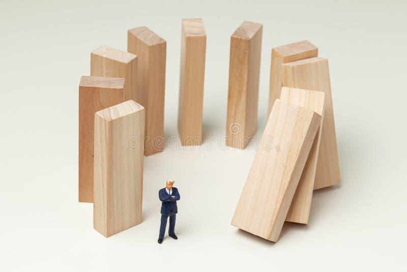 Karma jak spadajÄ…ce domino. Biznesmeni popchnÄ™li dominacjÄ™ i oczekujÄ… i analizujÄ… wyniki. Sytuacja niebezpieczna obrazy royalty free