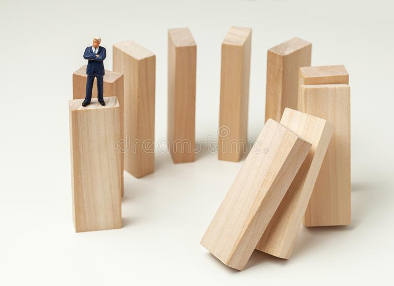Karma like falling dominoes. Businessman pushed dominoes and expects and analyzes the result. Dangerous situation royalty free stock photo