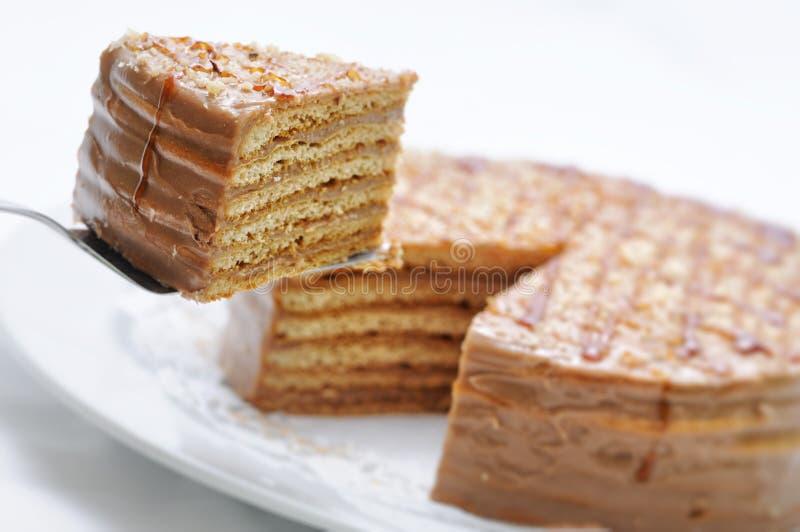 Karmelu tort z polewą na metal łyżce, urodzinowy tort na bielu talerzu, patisserie, fotografia dla sklepu fotografia stock