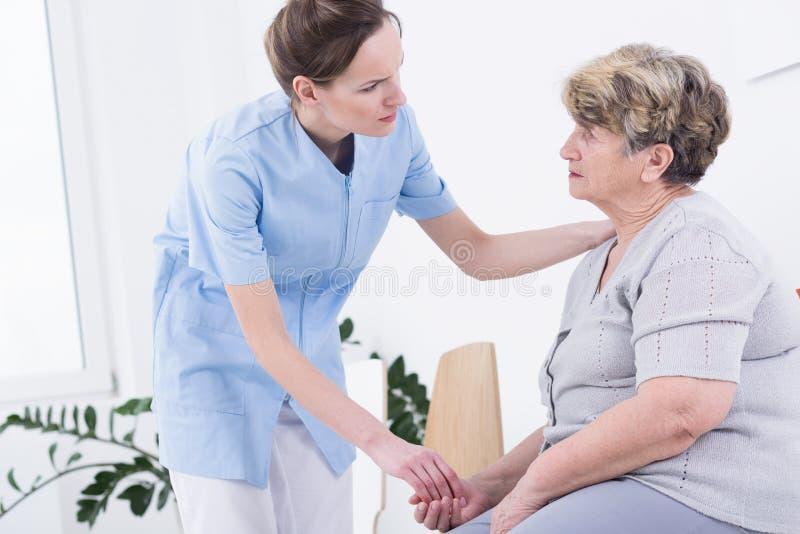 Karmiący domowej opieki emeryt i jej opiekun zdjęcia stock
