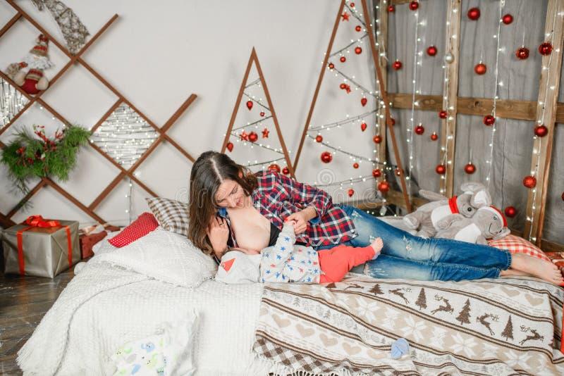 Karmienie piersią Święta zimowe Karmienie piersią Rodzina ubrana w kostiumy Mikołaja Święta zimowe obraz stock