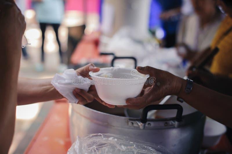 Karmienie potrzebujący w społeczeństwie: Pojęcie karmienie: Wolontariuszi dają jedzeniu bieda: darować jedzenie pomaga istoty lud obrazy stock