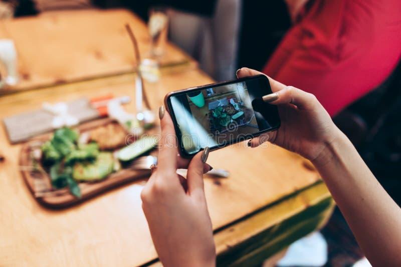 Karmowa fotografia dla ogólnospołecznych sieci Zakończenie wizerunek żeńskie ręki trzyma telefon z jedzeniem na parawanowym bierz obrazy royalty free