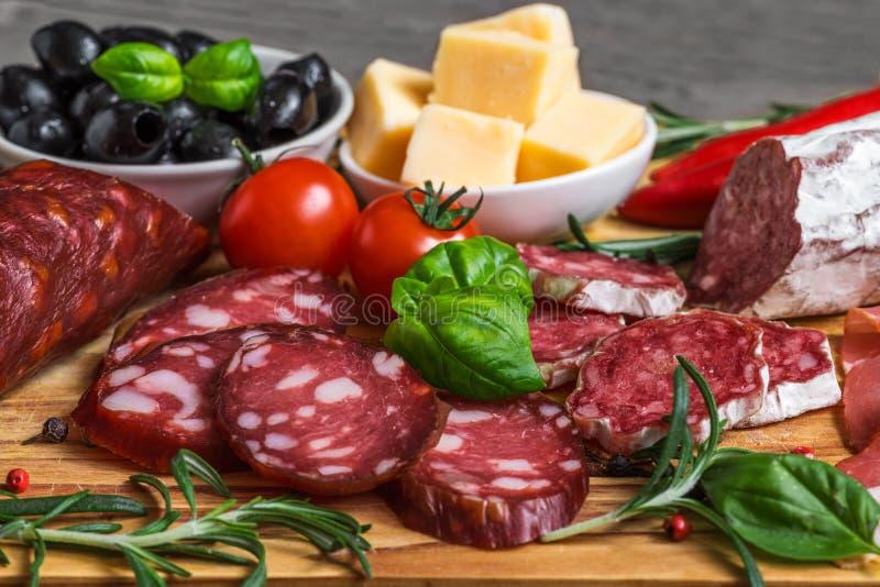 Karmowa taca z wyśmienicie salami, bekonem, serem, uwędzonymi kiełbasami, oliwkami, pomidorem i ziele, Mięsny półmisek na drewnia obrazy royalty free
