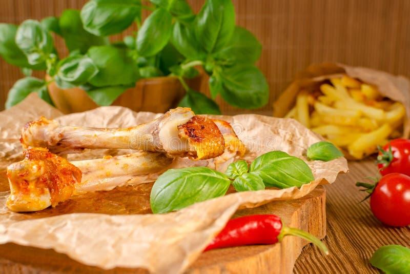 Karmowe resztki od piec na grillu kurczaka i chili z pomidorem, dłoniakami i basilem na drewnianym tle, fotografia stock