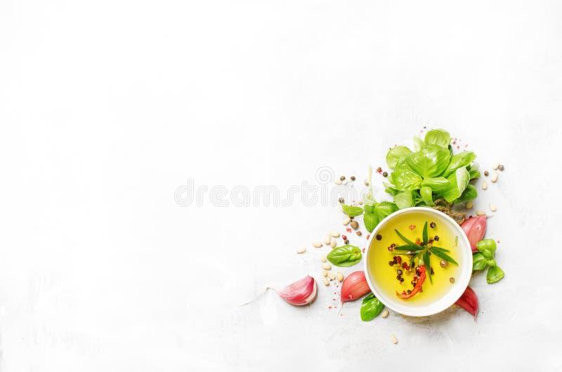 Karmowy kulinarny tło, oliwa z oliwek, cedrowe dokrętki, pikantność, ziele, zielony basil i menchia czosnek, mieszkanie nieatutow obrazy royalty free
