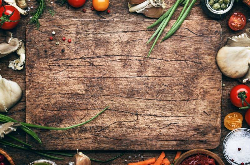 Karmowy kulinarny tło, składniki dla przygotowanie weganinu naczyń, warzywa, korzenie, pikantność, pieczarki i ziele, Stary rozci fotografia stock