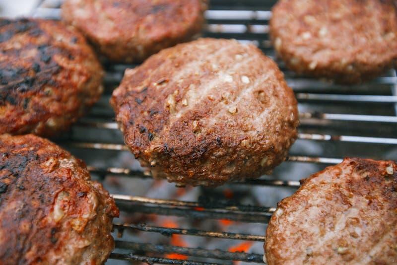 Karmowy mięso - wołowina hamburgery na bbq grillu piec na grillu z płomieniem zdjęcia stock