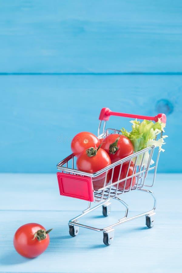 Karmowy minimalny pojęcie, naturalni organicznie pomidory w zabawkarskim wózku na zakupy na błękitnym drewnianym tle z kopii prze obraz royalty free