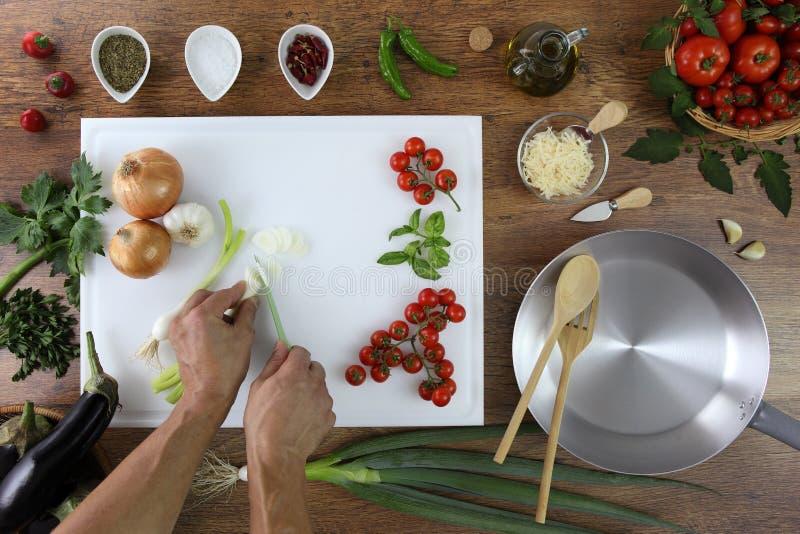 Karmowy odgórny widok, ręki ciie zieloną cebulę na białej ciapanie desce obrazy stock