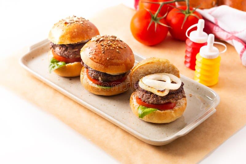 Karmowy pojęcie Domowej roboty wzmacnia hamburgery słuzyć na kwadrata talerzu na białym tle z kopii przestrzenią fotografia stock