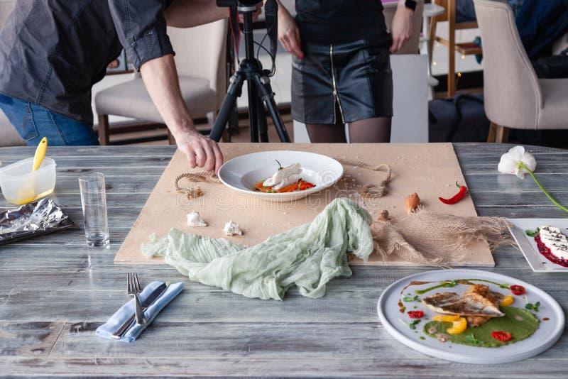 Karmowy stylista dekoruje, przygotowywaj?cy strzela? rybich naczynia z zielonego grochu puree, pomidor, pomara?cze plasterki Poj? obraz stock