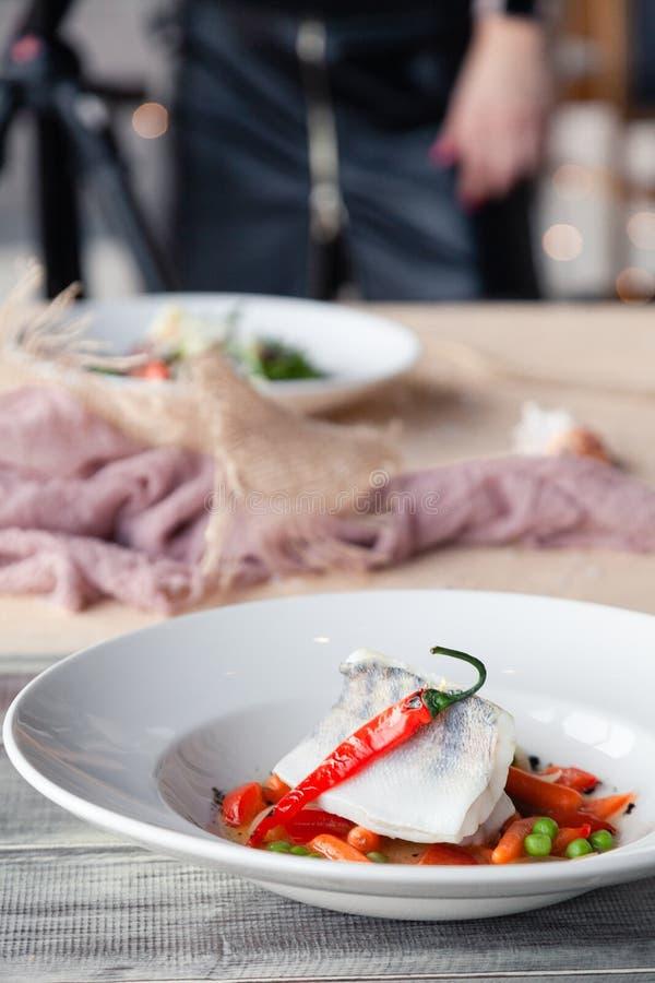 Karmowy stylista dekoruje, przygotowywaj?cy strzela? rybich naczynia z zielonego grochu puree, pomidor, pomara?cze plasterki Poj? fotografia stock