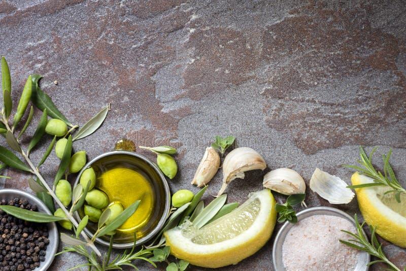 Karmowy tło z oliwkami, olejem, cytryną, czosnkiem, ziele i pikantnością, zdjęcia royalty free
