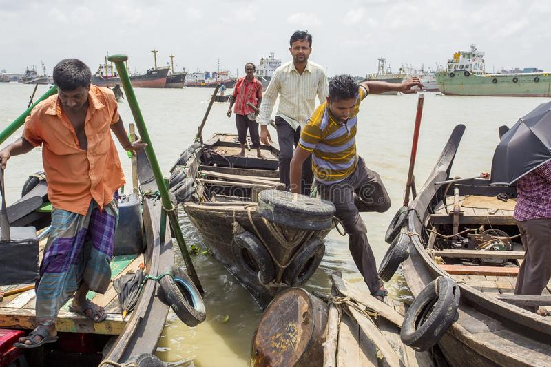 3 mans are lifting on boats in Karnafuli River Sadarghat areas, Chittagong, Bangladesh. Karnafuli River Sadarghat areas, Chittagong, Bagladesh. Chittagong is stock photos