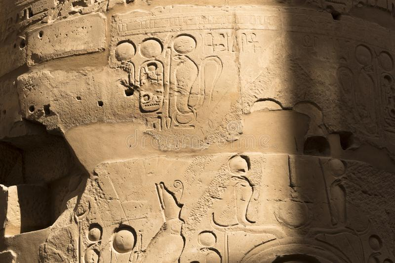 Karnak Temple, complex of Amun-Re. Embossed hieroglyphics on columns. Great Hypostyle Hall. Columns damaged by French vandal -soldiers during the colonization stock photography