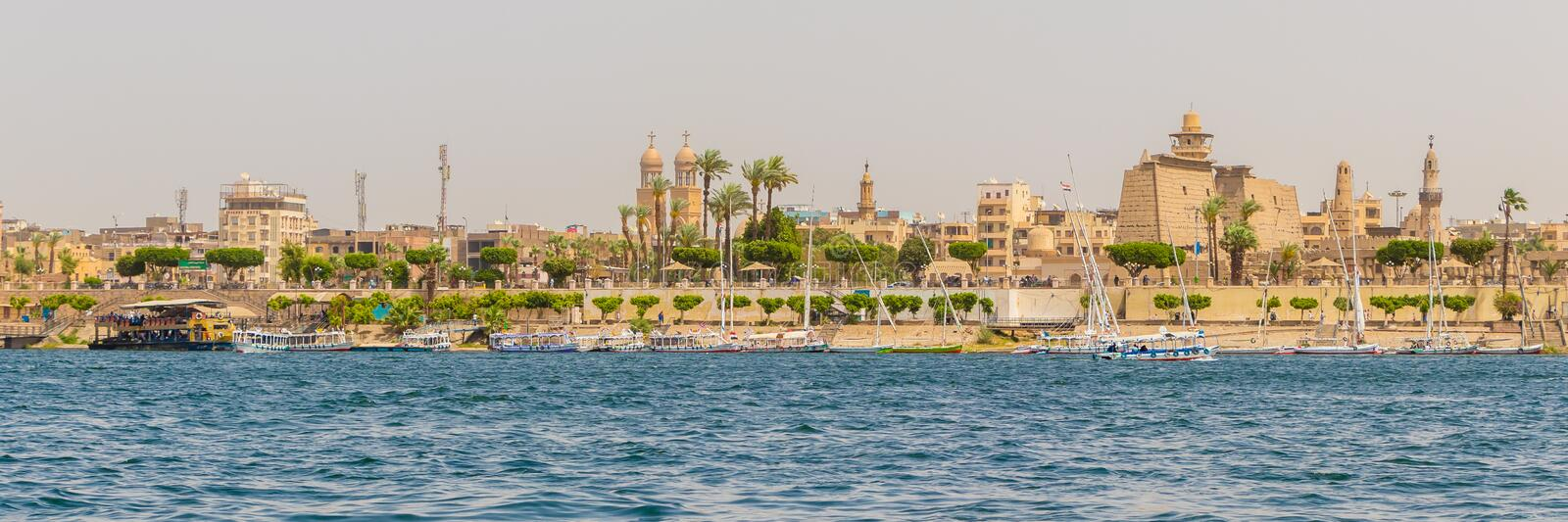 Karnak temple and the Muslim mosque on the banks of the river Nile in Luxor, Egypt. Luxor, Egypt - April 16, 2019: Karnak temple and the Muslim mosque on the royalty free stock image