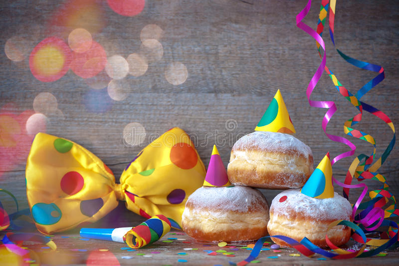 Karnawałowi donuts z papierowymi streamers i partyjnym łęku krawatem obrazy stock