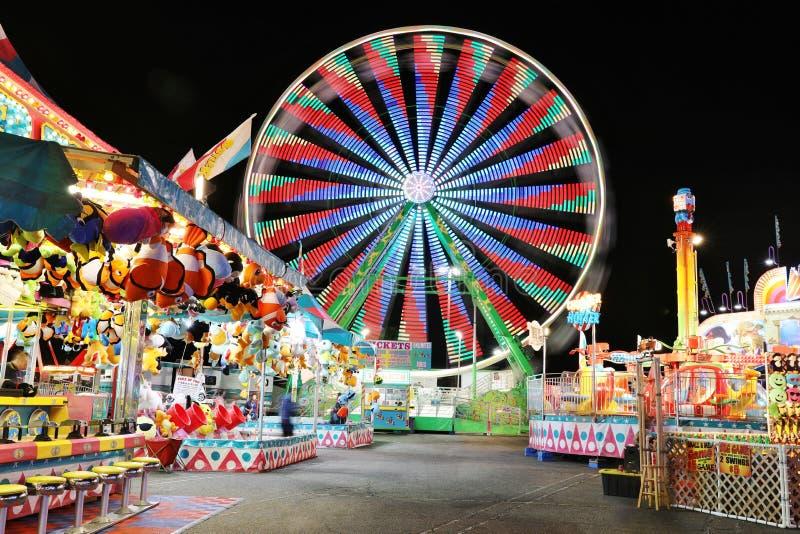 Karneval och Ferris Wheel på natten - ljusa ljus och lång exponering royaltyfri bild
