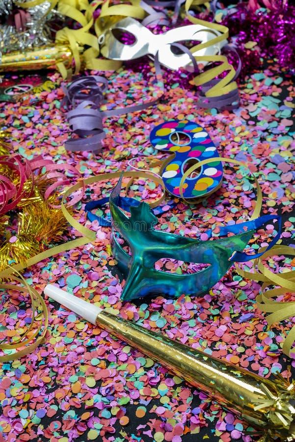 Karnevalhorn och blå karnevalmaskering över konfettier och mång--färgade banderoller royaltyfri fotografi