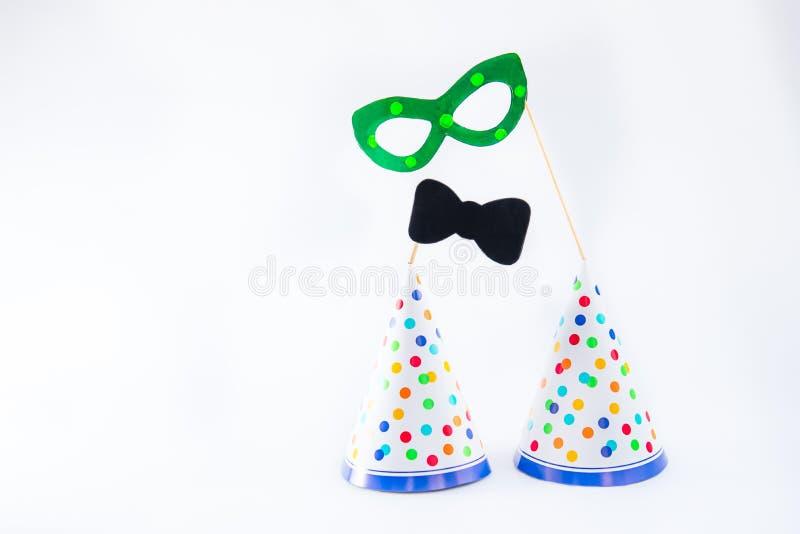 Karnevalskappen und lustige Masken auf einem weißen Hintergrund lokalisiert Parteiwerkzeuge und -dekoration Alles- Gute zum Gebur stockfotografie
