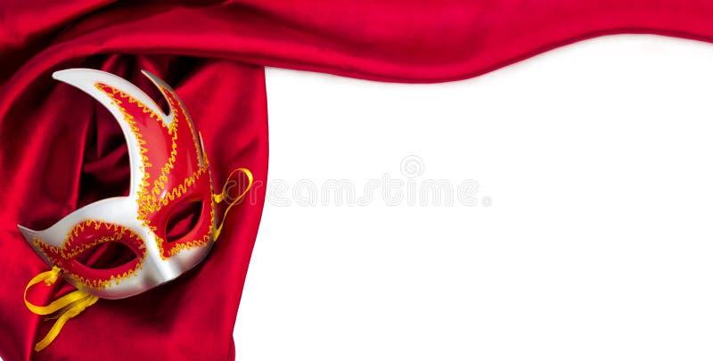 Karnevalsmaske und rotes Seidengewebe stockbilder