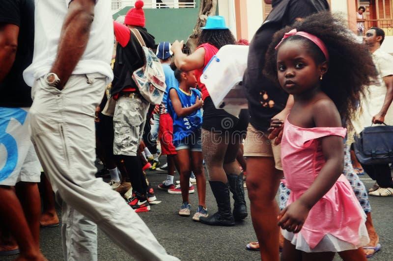 Karnevalsmenge, die auf die Straßen der Stadt mit einem netten kleinen Mädchen geht stockbild