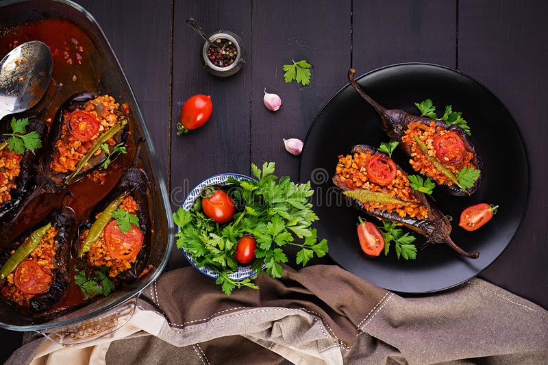 Karniyarik - turkish traditional aubergine eggplant meal. Stuffed eggplants with ground beef. And vegetables baked with tomato sauce. Turkish cuisine. Top view stock photography