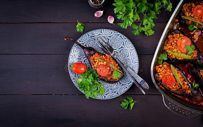 Karniyarik - turkish traditional aubergine eggplant meal. Stuffed eggplants with ground beef. And vegetables baked with tomato sauce. Turkish cuisine. Top view stock photos