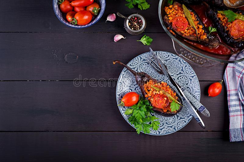 Karniyarik - turkish traditional aubergine eggplant meal. Stuffed eggplants with ground beef. And vegetables baked with tomato sauce. Turkish cuisine. Top view stock images