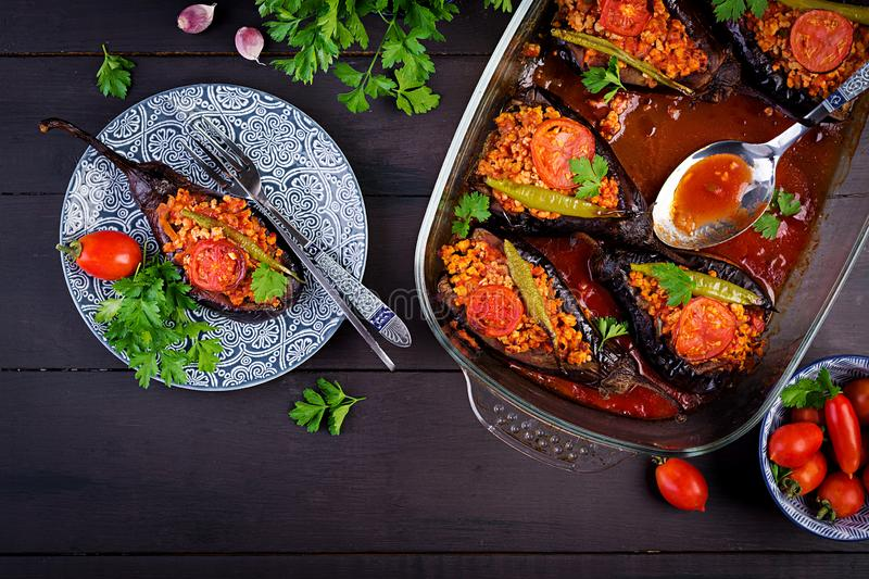 Karniyarik - turkish traditional aubergine eggplant meal. Stuffed eggplants with ground beef. And vegetables baked with tomato sauce. Turkish cuisine. Top view royalty free stock photo