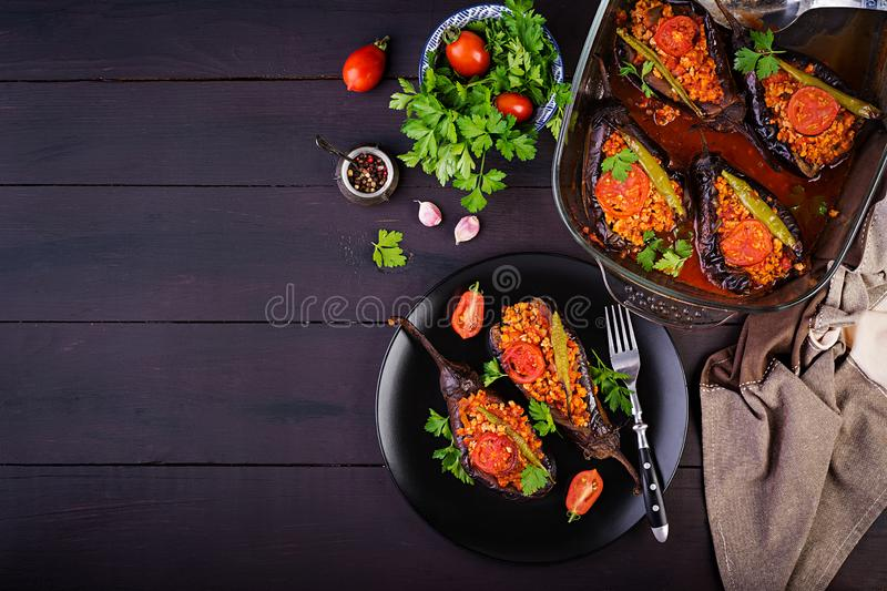 Karniyarik - turkish traditional aubergine eggplant meal. Stuffed eggplants with ground beef. And vegetables baked with tomato sauce. Turkish cuisine. Top view royalty free stock images