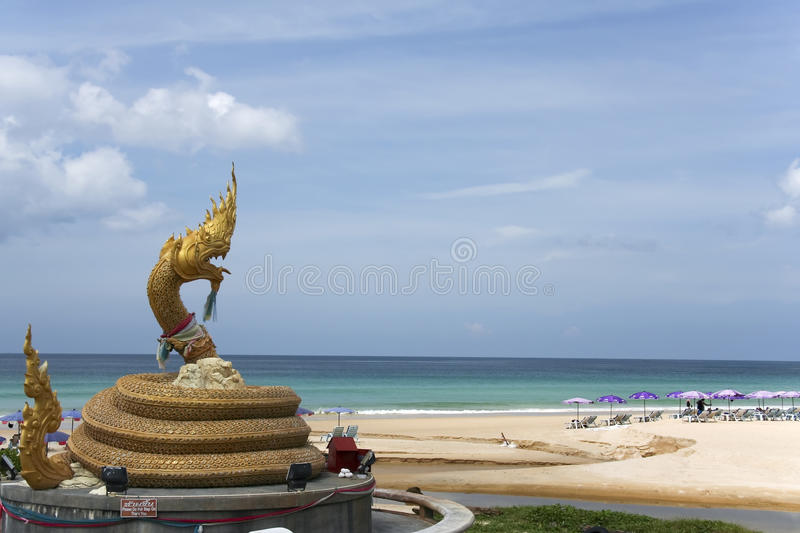 Karon beach naga statue landmark phuket thailand. Coiled golden naga statue on popular karon beach phuket thailand stock photography
