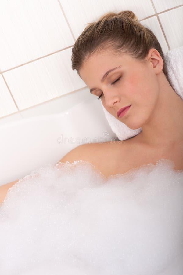 Karosseriensorgfaltserie - Frau, die in der Badewanne liegt lizenzfreies stockfoto