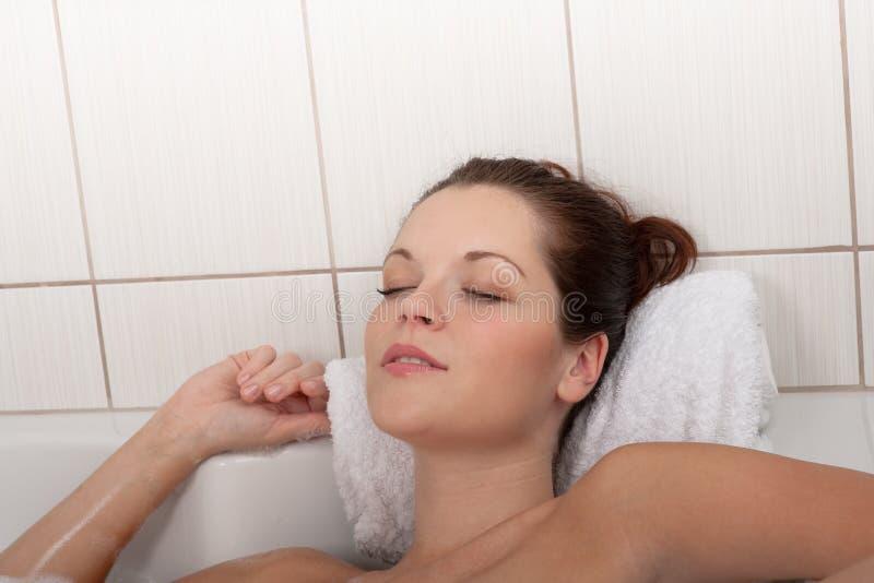 Karosseriensorgfaltserie - Frau, die in der Badewanne liegt stockfotografie