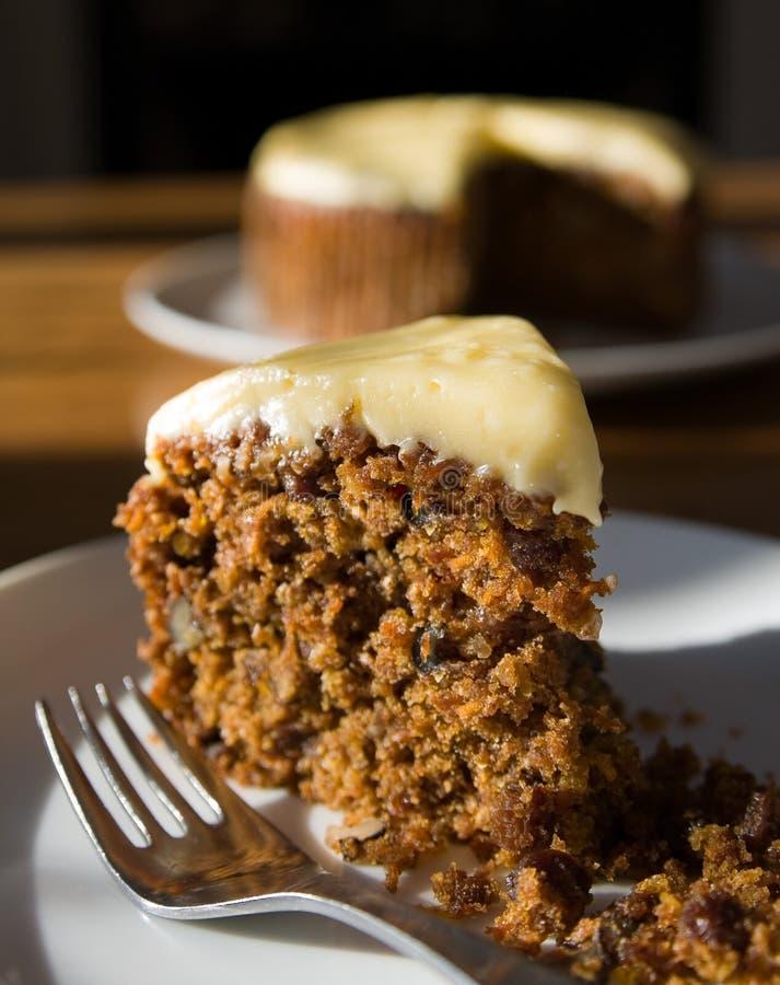 Karottekuchenscheibe mit Kuchen im Hintergrund lizenzfreie stockfotos