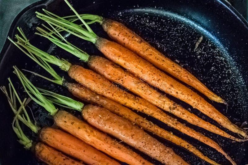 Karotten in der schwarzen Bratpfanne stockbild