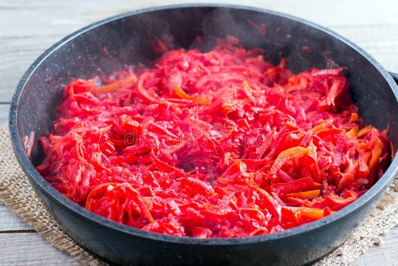 Karotten, rote Rüben und Zwiebel in einer Bratpfanne werden auf dem Ofen gebraten Bestandteile für Borschtsch stockfoto