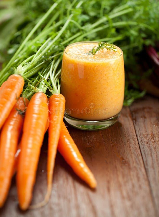 Karottensaft im gesunden Lebensmittel der Glas- und frischen Karotten auf einem grauen Steinhintergrund stockfoto