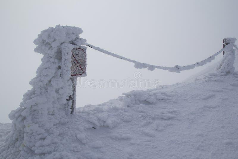 Karpacz, Polonia - 03 20 2016: Prohibición de la muestra del paso cubierta con nieve con niebla en el fondo en el pico de Sniezka imagenes de archivo