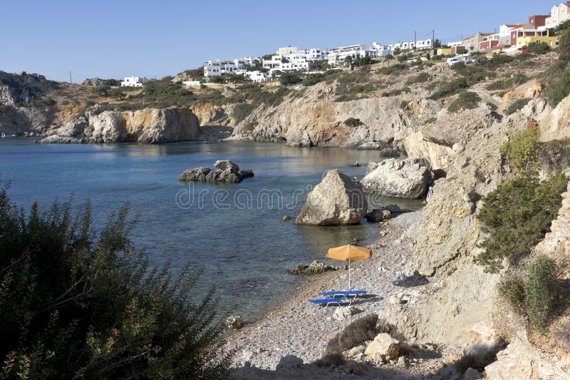 Karpathos island, small pebbles beach and umbrella in Amopi bay. Aegean sea, Dodecanese Islands, Greece. Quiet small beach with sunbathing beds near Pigadia royalty free stock photo