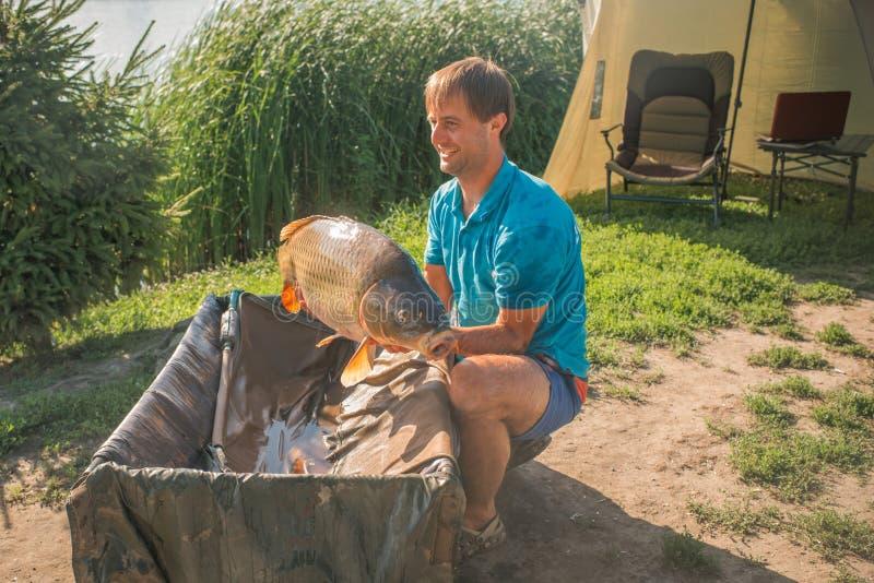 Karper en Visser, Karper visserijtrofee stock afbeeldingen