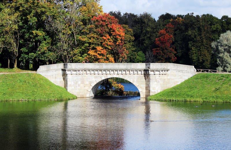 Karpin bro - som förbinder ön i Gatchina Lokaliserat på en konstgjord kaskad mellan dammet och den vita sjön royaltyfria foton
