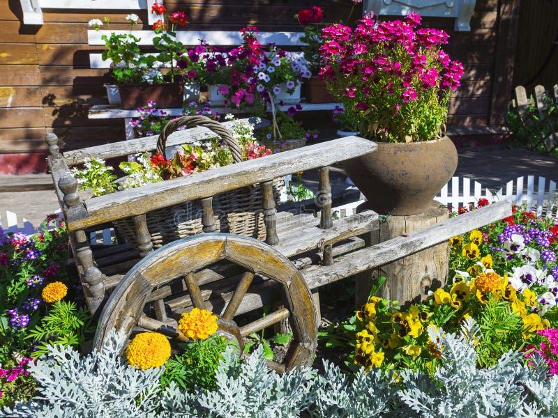 Karretje met mooie bloemen in de tuin stock foto's