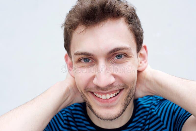 Karrierefreier junger Mann lächelt mit Händen hinter Kopf stockbild