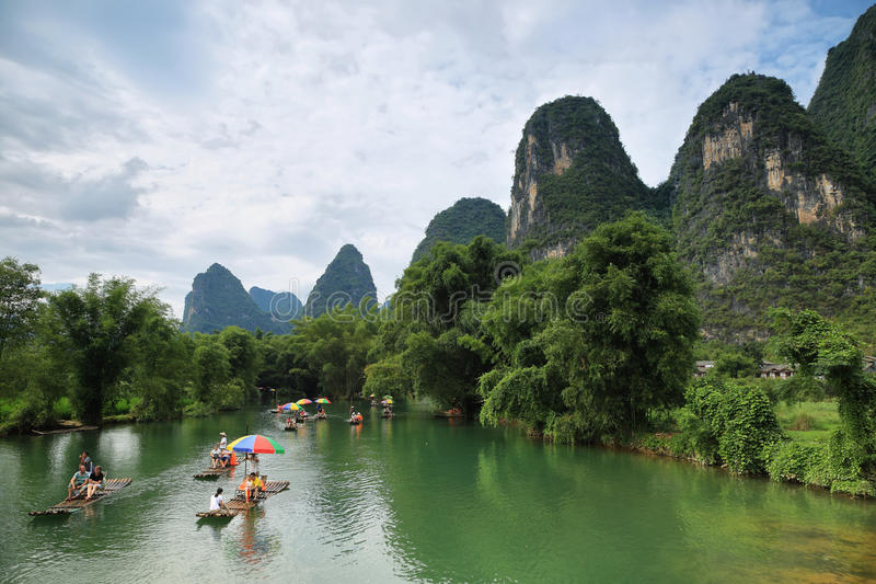 Karst mountains reflected in Yulong river. YANGSHUO, CHINA - SEPTEMBER 19, 2015: Tourist people sailing on traditional bamboo rafts and karst mountains reflected stock image