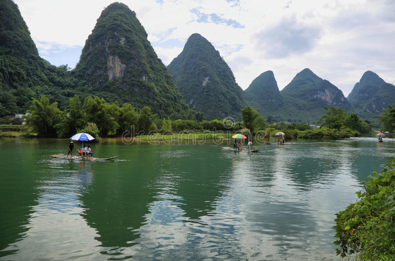 Karst mountains reflected in Yulong river. YANGSHUO, CHINA - SEPTEMBER 19, 2015: Tourist people sailing on traditional bamboo rafts and karst mountains reflected royalty free stock photo