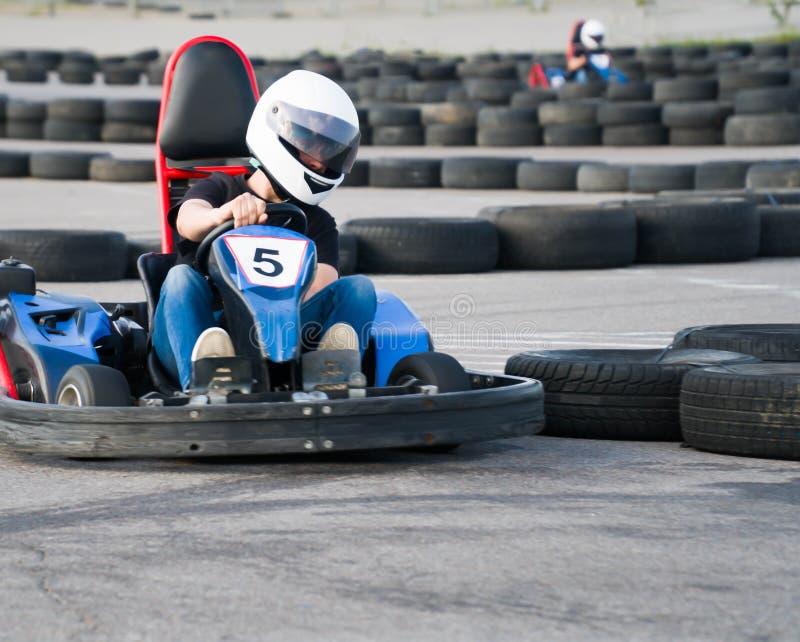 Kart som korsar mållinjehandlingen, hastighet, hjälm, spår, chaufför, konkurrens, motor, rörelse, adrenalin arkivbilder