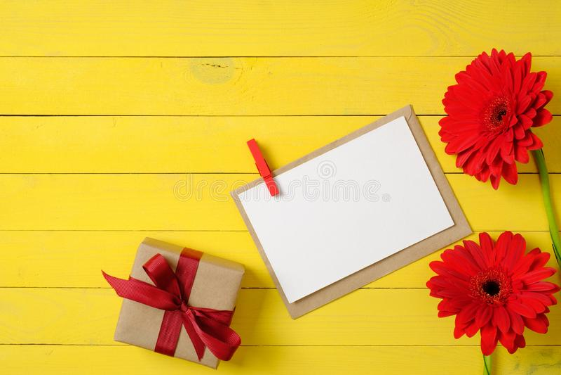 Karte des leeren Papiers mit Stift, Gänseblümchenblumen und Geschenkbox mit Bandbogen auf gelbem Hintergrund Glückwunsch- oder Fe stockfoto