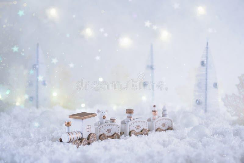 Karte des neuen Jahres mit Spielzeugzug in einem feenhaften Wald auf Winterhintergrund mit Schnee und Lichtern lizenzfreies stockfoto